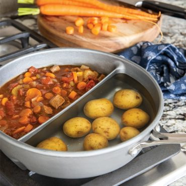Divided sauce pan on stovetop with boiling potatoes and stew