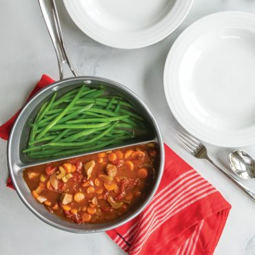 Stew and green beans in divided sauce pan with dinner plates