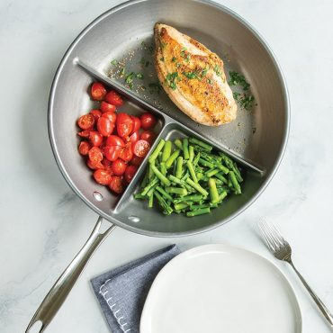 Three section divided skillet with cooked tomatoes, chicken and vegetables with plates on the side