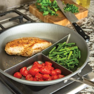 3-in-1 divided saute pan on stovetop with cooked food
