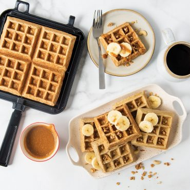 Plated banana oat waffles with peanut butter syrup and coffee scene