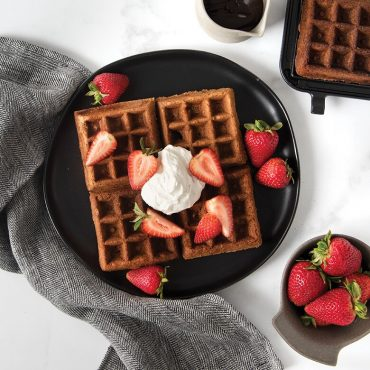 Plated chocolate waffles with whipped cream and strawberries