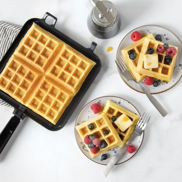 Classic Waffle plated with syrup, butter and berries. Cooked waffle on waffler