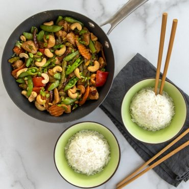 """Cashew vegetable and chicken stir fry in 8"""" Wok with two bowls of rice on the side with chop sticks."""