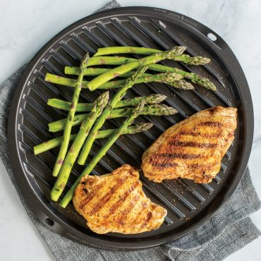 Grilled asparagus and chicken on grill side of griddle, with towel