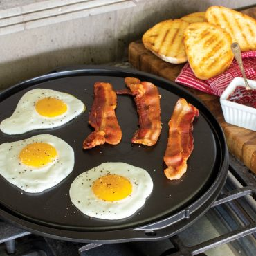 Fried eggs and bacon on flat griddle side on stovetop