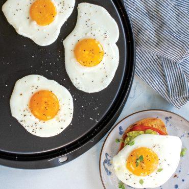 Fried eggs on flat griddle side, egg on toast, on plate