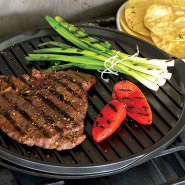 Grilled steak, peppers, onions on round griddle on stovetop