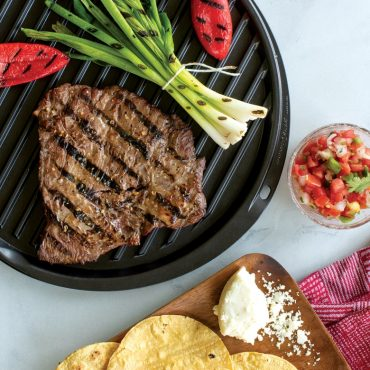 Grilled steak, peppers, onions on grill side of griddle, tortillas and salsa on the side