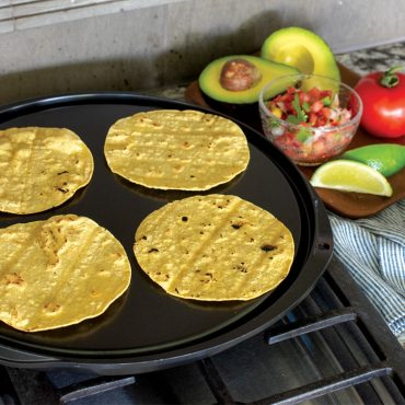 Corn tortillas on flat side of griddle on stovetop, heating