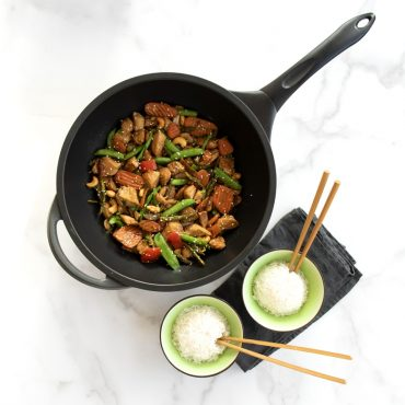 Chicken, cashew, and vegetables stir fry in Procast Wok with two rice bowls on the side