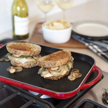 Grilled cheese sandwiches with onions on slim griddle on stovetop