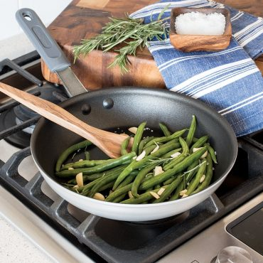 """Cooked green beans in 10"""" skillet on stovetop, cutting board and bowl of salt on the side."""