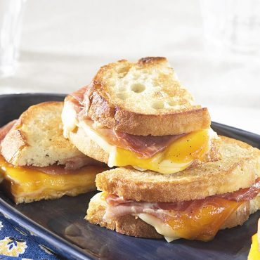 Grilled ham and cheese sandwiches on griddle