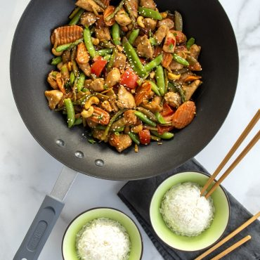 Chicken and vegetables stir fry with sesame seeds and cashews in Wok.