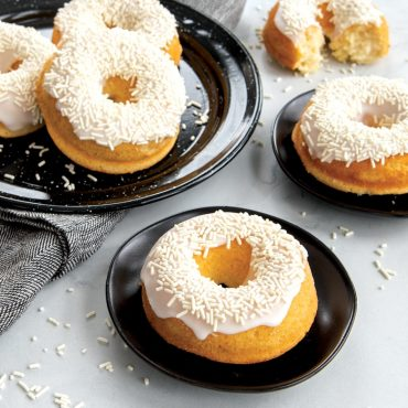 Baked vanilla donuts on plates with white glaze and white sprinkles