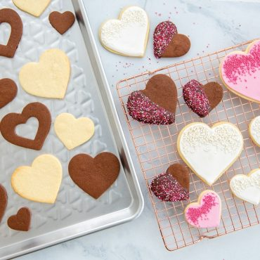 Baked heart shaped cookies on pan, decorated heat cookies on cooking rack