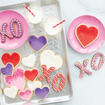 Decorated heart cookies and milk served on heart embossed pan