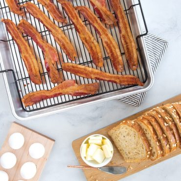 Baked bacon on Extra Large Oven Crisp Baking Tray, sliced bread on cutting board