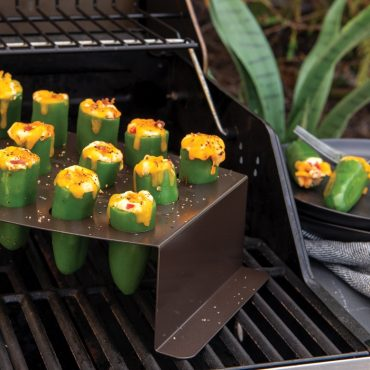 Grilled cheese stuffed jalapeno pepper in stand on grill