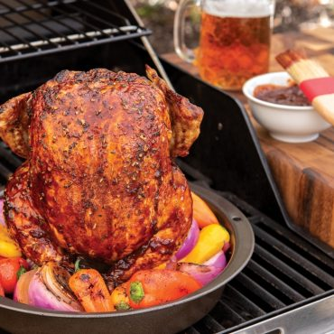 Grilled whole chicken on roaster with vegetable in pan, on grill