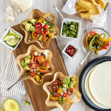 3 cooked tortilla bowls filled with rice and fajitas, condiments on the side