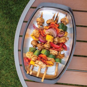 Grilled veggie and chicken kabobs on grill n' serve plate on outdoor table.