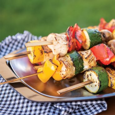 Closeup of kabobs on grill n' serve plate with towel