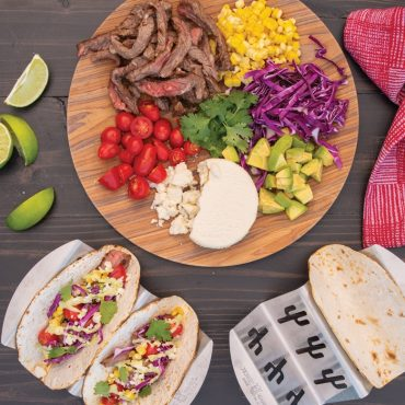 Grilled fajita scene with two taco racks filled with grilled tortillas and filled with toppings.