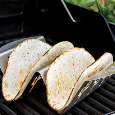 Two flour tortilla on taco rack on grill