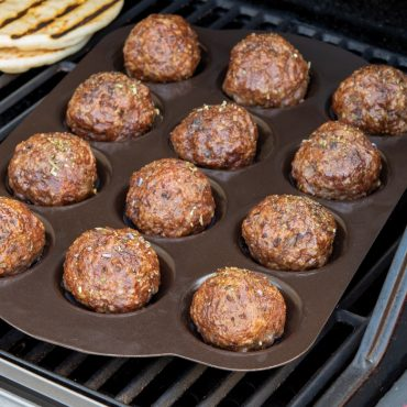Grilled meatballs in pan on grill