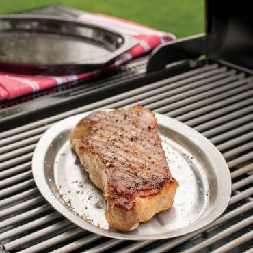 Grilled steak on stainless steel tray, on grill