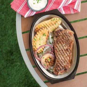 Server with grilled steak, vegetables