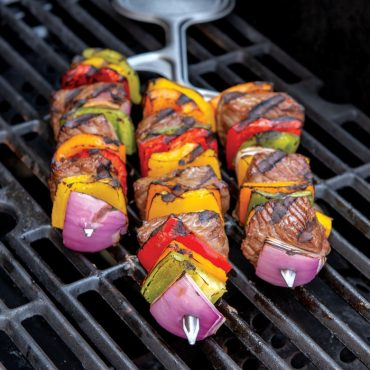 Skewer filled with beef and vegetable on grill