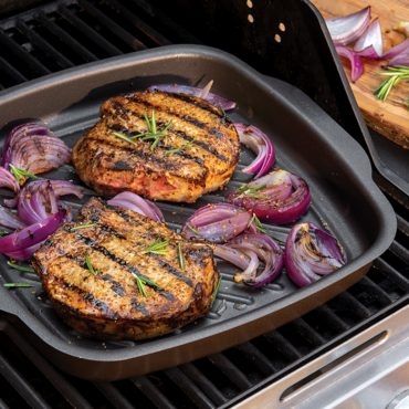 Grilled pork chops, onions, in griddle pan on grill