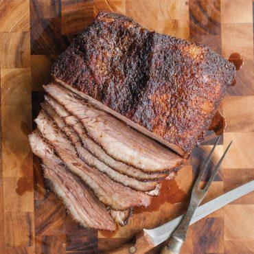 sliced smoked brisket on cutting board