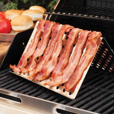 Bacon laid over grill tent, on grill