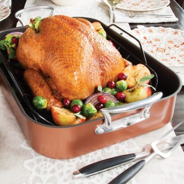 Cooked turkey on rack in roaster with vegetables