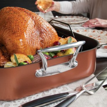 Close up cooked turkey in roaster, carving tools