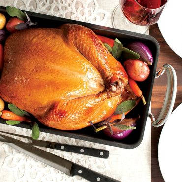 Cooked whole chicken with vegetables in roaster
