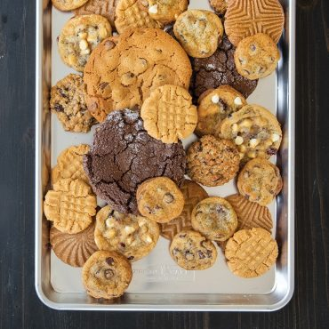 Variety of baked cookies piled on half sheet