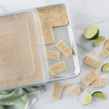 Baked shortbread in pan with lid with lime wedges