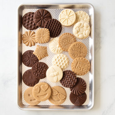 Stamped cookies in different designs scattered on half sheet