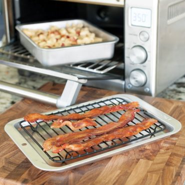 Casserole pan with food in toaster oven, sheet pan with bacon on rack