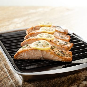 Broiled salmon steaks with dill and lemon on grill pan