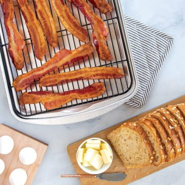 Baked bacon on bacon pan, oatmeal bread and butter, eggs