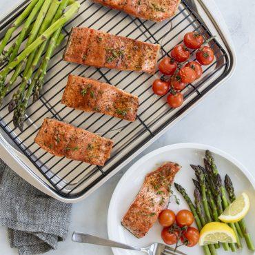 Baked salmon, asparagus, tomatoes on bacon pan, salmon, asparagus, tomatoes, lemon on plate