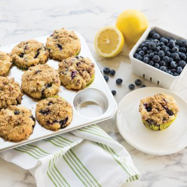 baked blueberry muffins in pan, one muffin on plate, fresh blueberries an lemons on counter