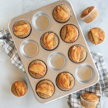 baked cinnamon muffins with apple slice garnish on muffin pan