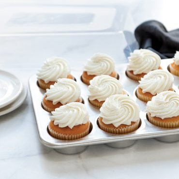Baked and frosted vanilla cupcakes in pan, lid in background